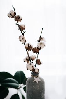 Cotone bianco bello secco e soffice su fondo di legno bianco con spazio di copia. il cotone è una sostanza fibrosa morbida di una pianta tropicale ed è usato come fibra tessile, filo per cucire e fare stoffa.