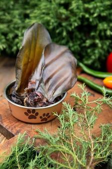Spighe di manzo essiccate nella nave per cani tra il verde sulla tavola di legno. dolcetti da masticare per cani domestici.