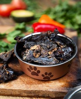 Fegato di manzo essiccato nel vaso del cane tra il verde sulla tavola di legno e alcune verdure sullo sfondo. dolcetti da masticare per cani domestici.
