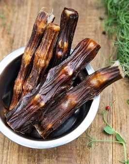 Coda di manzo essiccata nella nave cane tra il verde sulla tavola di legno. dolcetti da masticare per cani domestici.