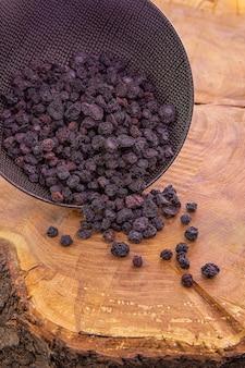 Mirtillo essiccato versato da una tazza scura su un tavolo di legno