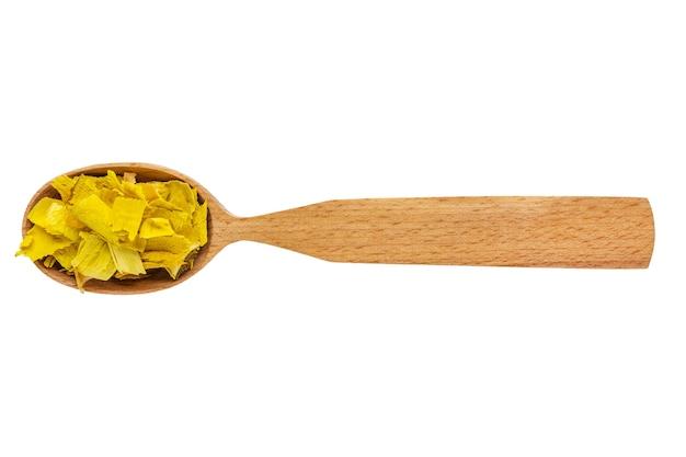 Radice di burberry essiccata in un cucchiaio di legno isolato su uno sfondo bianco