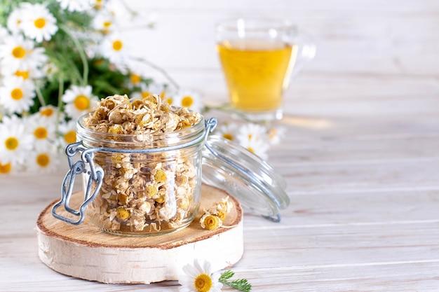 Camomilla secca nel vaso sulla tavola di legno bianca. tè alla camomilla biologica in tazza e fiori. copia spazio