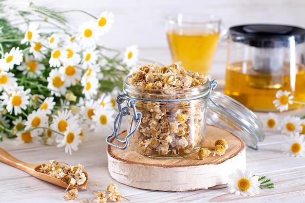 Camomilla secca nel vaso sulla tavola di legno bianca. tè alla camomilla biologica in tazza e fiori