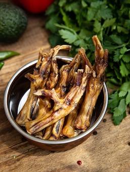 Cosce di pollo essiccate nella nave per cani tra il verde sulla tavola di legno e alcune verdure sullo sfondo. dolcetti da masticare per cani domestici.