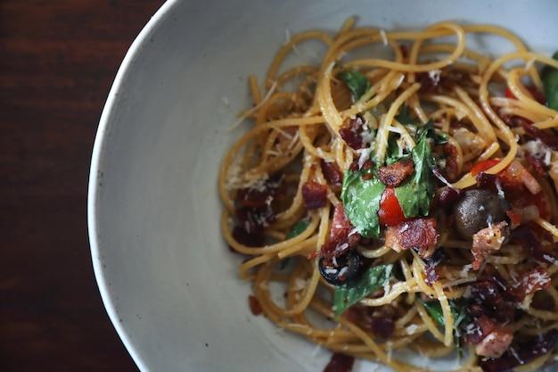 Spaghetti al peperoncino rosso e pancetta secchi sulla tavola di legno