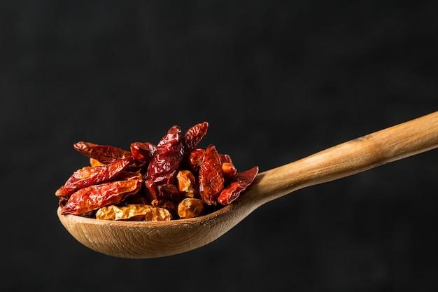 Condimento secco di chili peppers in un cucchiaio di legno