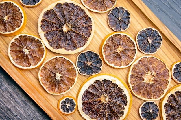 I pezzi di agrumi essiccati sono disposti su una tavola di legno per il trasferimento del prodotto. cibo vitaminico