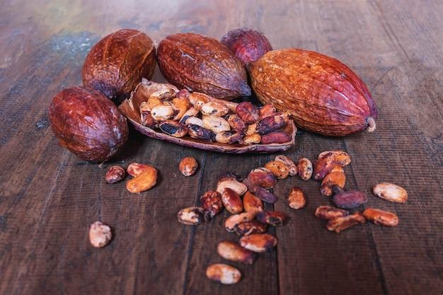 Frutta secca del cacao e fave di cacao secche su vecchio fondo di legno