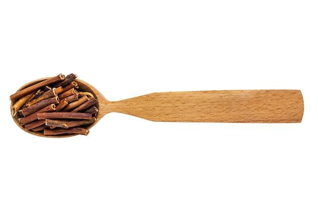 Comarum palustre essiccato in un cucchiaio di legno su uno sfondo bianco.