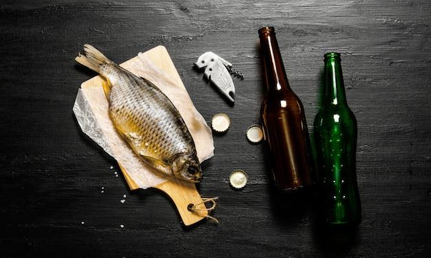 Pesce essiccato e bottiglie di birra sul bordo nero. vista dall'alto