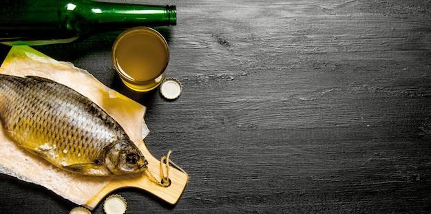 Pesce essiccato e birra fresca su una lavagna