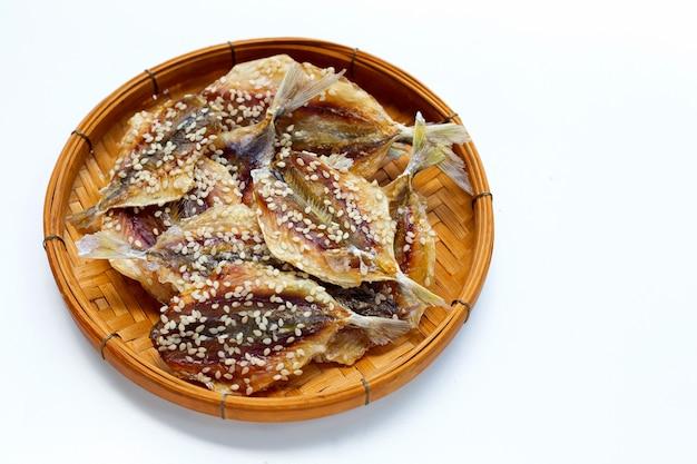Pesce essiccato con semi di sesamo in cesto di bambù su sfondo bianco.