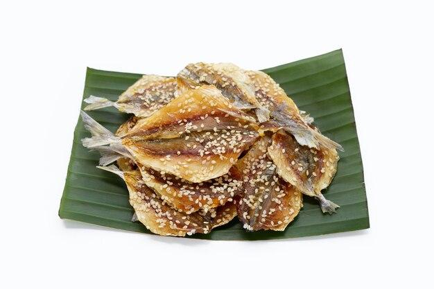 Pesce essiccato con semi di sesamo su foglia di banana su sfondo bianco.