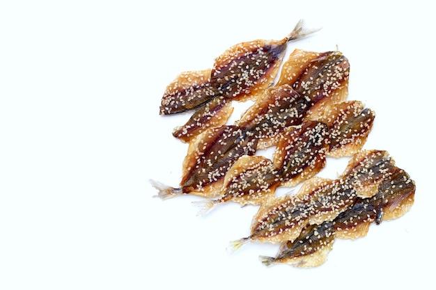 Pesce essiccato con semi di sesamo su sfondo bianco.