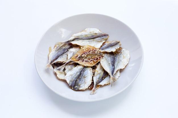 Pesce essiccato con semi di sesamo in piastra bianca su sfondo bianco.