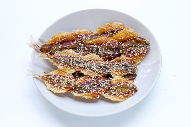 Pesce essiccato con semi di sesamo in piatto bianco su sfondo bianco.