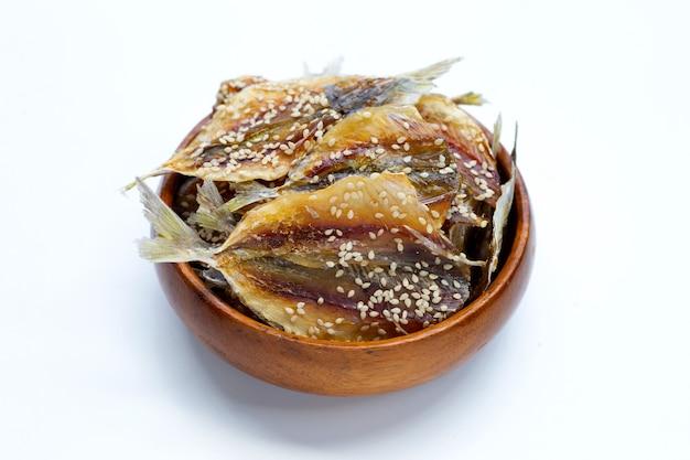 Pesce essiccato con semi di sesamo in ciotola di legno su sfondo bianco.