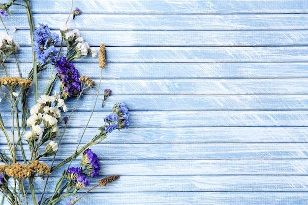 Fiori secchi sulla superficie di tavole di legno colorate