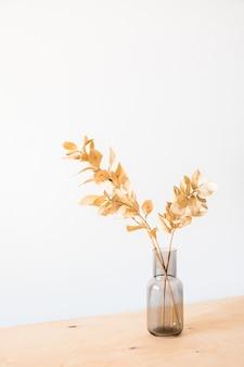 Fiori secchi in un vaso di vetro con una parete chiara vuota
