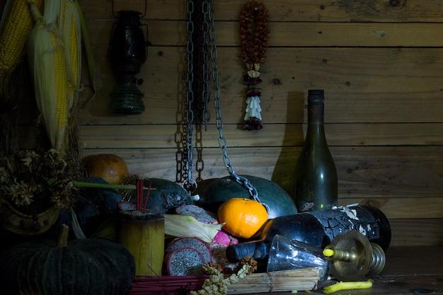 Essiccato di frutta e bottiglia su legno in camera con luce fioca.