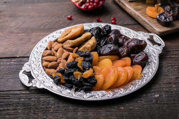 Frutta secca e noci si mescolano in una ciotola di legno