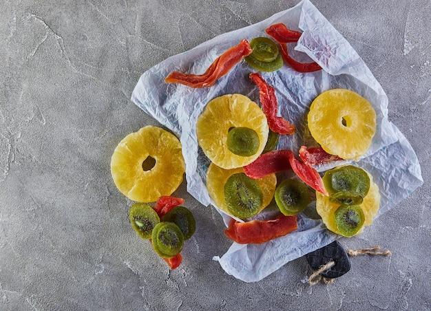 Frutta secca: anelli di ananas canditi gialli, papaia rossa e kiwi verde su carta da imballaggio bianca su cemento grigio