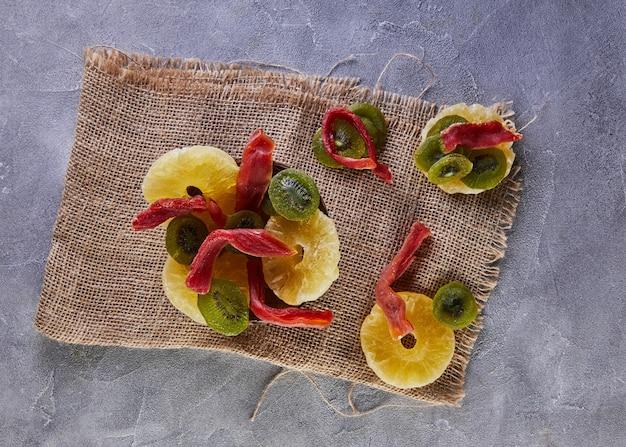 Frutta secca: anelli di ananas canditi gialli, papaia rossa e kiwi verde in un piatto di legno su tela
