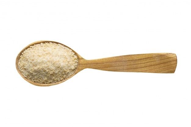 Aglio in polvere essiccato da aggiungere al cibo. spezie in cucchiaio di legno isolato su bianco.