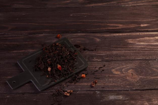 Foglie di tè verde essiccate su fondo di legno