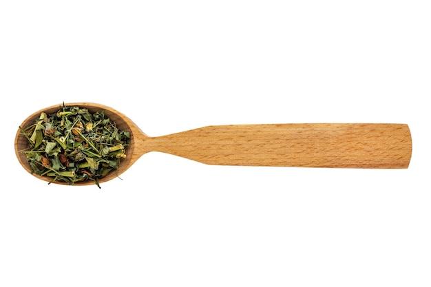 Iperico essiccato in un cucchiaio di legno su uno sfondo bianco.