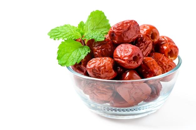 Giuggiola essiccata, frutta secca cinese data rossa con foglie di menta in tazza di vetro isolato su bianco, frutti di erbe.