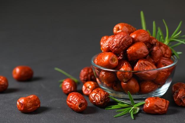 Giuggiola essiccata, frutta rossa secca cinese con foglia di rosmarino in tazza di vetro su sfondo nero, frutta a base di erbe.