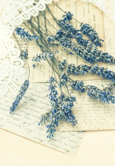 Fiori di lavanda essiccati, pizzi e vecchie lettere d'amore. nostalgia. foto dai toni in stile retrò. messa a fuoco selettiva