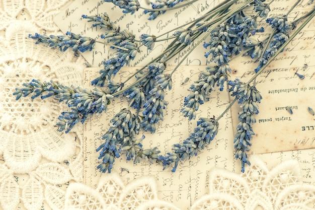 Fiori di lavanda secchi e cartoline d'amore vintage. nostalgica natura morta. immagine dai toni in stile retrò