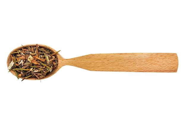 Ledum essiccato o subsezione di rododendro in un cucchiaio di legno su uno sfondo bianco.