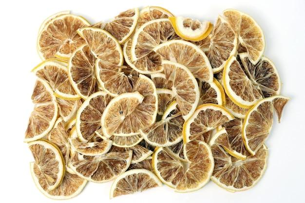 Il primo piano secco delle fette di limone su fondo bianco. cibo salutare vitaminico utile