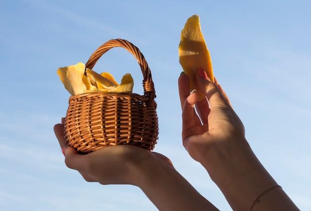 Mango essiccato in un cesto di vimini nelle mani di una ragazza contro il cielo.
