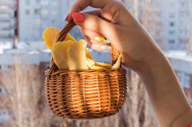 Mango essiccato in un cesto di vimini nelle mani di una donna