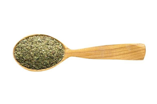 Menta secca da aggiungere al cibo. spezia in cucchiaio di legno isolato su bianco. condimento del pasto delizioso.