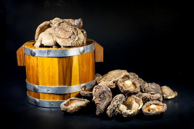Funghi secchi in una cassa di legno su sfondo nero