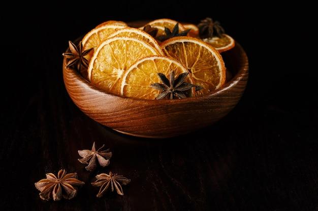 Fette di arancia essiccate in un piatto di legno.