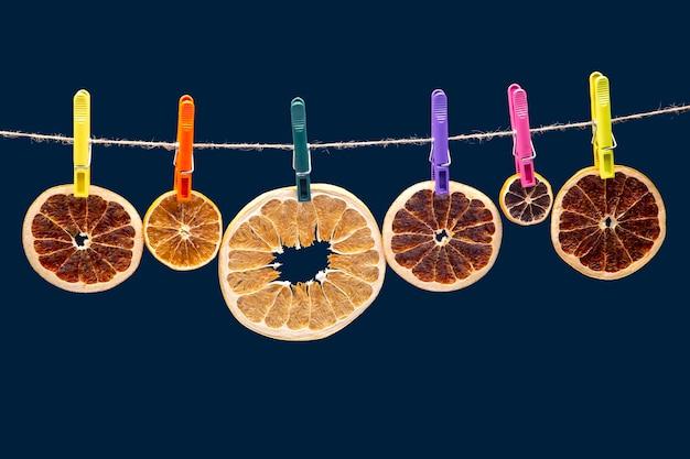 Pezzi secchi di diversi agrumi sono appesi a mollette colorate