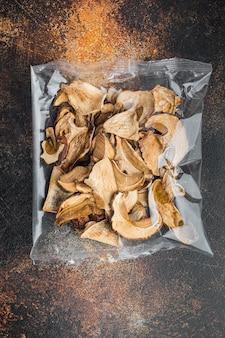 Set di funghi porcini secchi, sul vecchio fondo rustico scuro, in confezione di plastica, vista dall'alto laici piatta