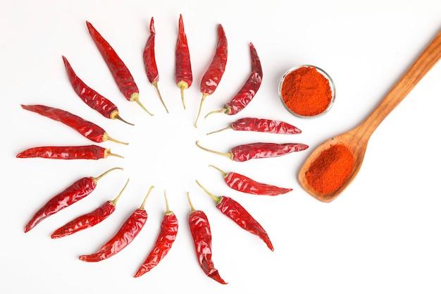 Peperoncino rosso secco e polvere nella ciotola di vetro sulla superficie bianca