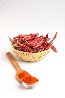 Ciotola di legno di peperoncino rosso secco sulla superficie bianca