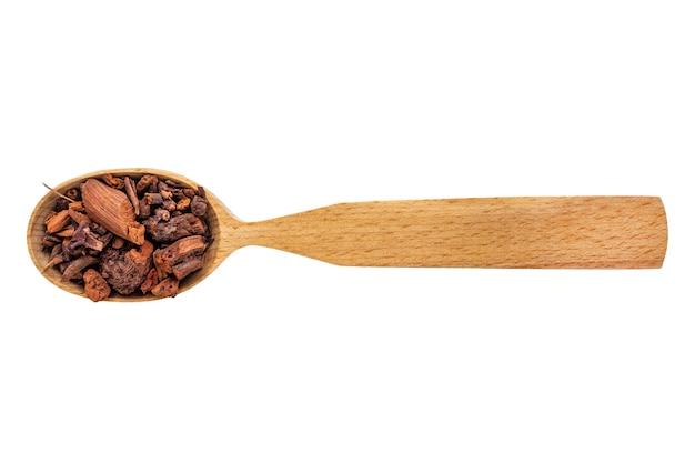 Rubia essiccata in un cucchiaio di legno isolato su uno sfondo bianco
