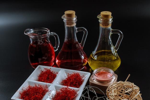 Filetti di zafferano essiccati su un piatto bianco ed estratto di olio.
