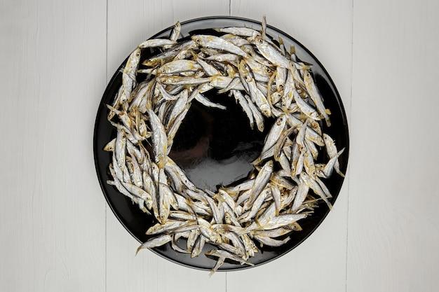 Pesce piccolo salato essiccato sulla banda nera sopra fondo di legno bianco, vista dall'alto. spuntino alla birra.
