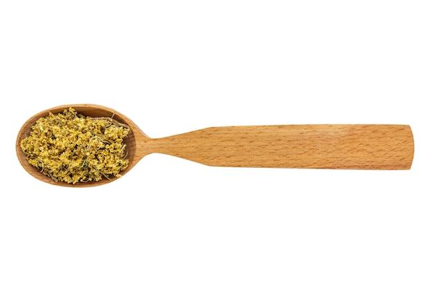 Sambuco essiccato o sambuco in un cucchiaio di legno su uno sfondo bianco.